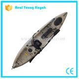 O caiaque profissional da pesca senta-se na canoa superior do mar com leme
