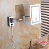 Lo specchio LED di rettangolo illumina lo specchio fissato al muro della stanza da bagno