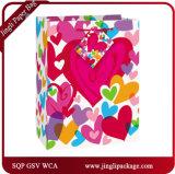 El regalo del brunch empaqueta las bolsas de papel florales del regalo con la maneta de la cinta del satén