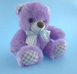 Urso enchido da peluche com fita roxa