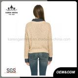 女の子は骨がある穀物の長い袖のクリームのセーターを暖める