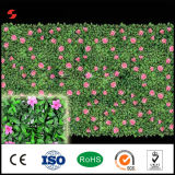 El nuevo verde del diseño barato deja la cerca artificial del seto con las flores al aire libre