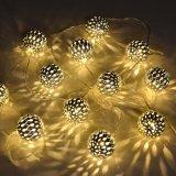 مسيكة شمسيّ يزوّد [لد] كرة خيط أضواء لأنّ حديقة فناء