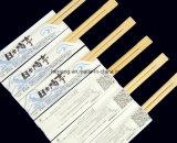 食品等級のペーパーによって包まれる使い捨て可能なタケ箸を水平にしなさい