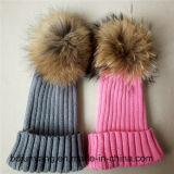 毛皮のポンポンが付いている冬のかぎ針編みの帽子によって編まれる帽子
