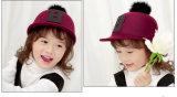 子供の赤ん坊は秋の冬のピークハンチング帽子のポンポンの球の騎手の帽子をからかう