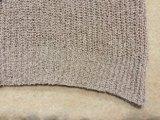 女性はひもで締める穀物のCamiのセーターの上を編んだ