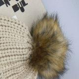 大きいポリエステル毛皮の球POM Pomsが付いている帽子の冬のニットの帽子を編んでいる男の子