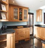 シンプルな設計の黒いカウンタートップが付いている木の食器棚