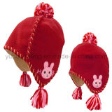 冬の子供の編むウールの球が付いている北極の羊毛の帽子か帽子