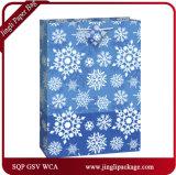 品質表示票およびサテンのリボンのハンドルが付いているクリスマスのショッピングギフトの紙袋