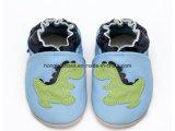 青い編まれた赤ん坊靴の恐竜