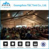 300 людей раскрывают обрамленный шатер для напольных банкета и партий