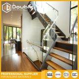 Escaleras de madera de interior de la pisada con la escalera moderna del pasamano de cristal