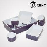 un ensemble de vaisselle de porcelaine colorée par famille comprenant des cuvettes et des plateaux