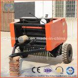 干し草の梱包機のあたりで運転されるトラクター