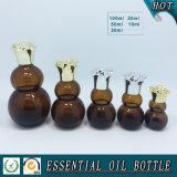 Bouteille en verre d'huile essentielle ambre de courge avec le couvercle de fleur