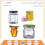Vasi esagonali di vetro di piccola dimensione del miele con le protezioni