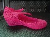 中国。 トンコワンはプラスチック靴を作るための注入機械に蹄鉄を打つ