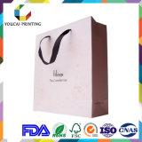 Bolsa de papel de la ropa que hace compras rectangular de lujo con insignia grabada oro de encargo