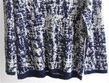 女性は長い袖のプルオーバーによって編まれたセーターを模造した