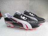 Schwarzes mit Weiß färbt im Freienfußball-Schuhe