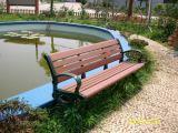 手すりおよびあと振れ止めが付いている庭の鋳鉄のベンチ