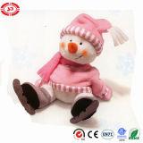 Bonhomme de neige rose de ski se reposant avec le jouet de Noël de la CE de peluche de patin