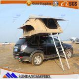 屋外の折るグループのキャンプ車の屋根のテント