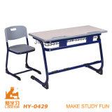 Mesa e cadeira elevadas da escola dos assentos dobro