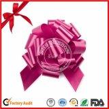誕生日プレゼントの包装のための装飾のリボンの赤いポンポンの引きの弓