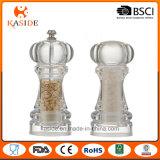 A mão plástica acrílica opera o moinho de sal e de pimenta