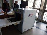 Segurança que seleciona a máquina da bagagem da raia X