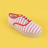 Donne rosse e scarpe di tela a strisce bianche delle scarpe da tennis della piattaforma degli appartamenti