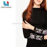 O首の刺繍が付いている黒によって編まれる長い袖のセーター