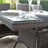 ガラスが付いている家具の灰色の柳細工の正方形表を食事する庭のテラスの居間