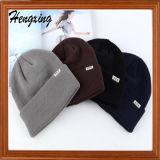 パッチによって編まれる帽子が付いている赤い編まれた帽子の帽子