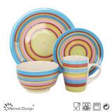 Main peignant l'ensemble coloré normal de vaisselle