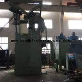 Singola macchina ad uncino di granigliatura con il pezzo in lavorazione