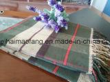 編まれた格子縞の純粋な綿のソファーによって縁を付けられる投球