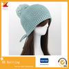 ポンポンが付いている冬の帽子を編んでいる女性