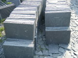 安く自然な石塀は黒く大きい長方形のスレートをタイルを張る