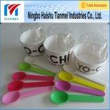 Taza del yogur con la tapa de la bóveda y la cuchara del yogurt congelado