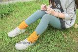 L'inverno bello della ragazza colpisce con forza i calzini del cotone con il bello tessuto del contrassegno