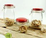 ガラス容器の赤い陶磁器のふたのガラス製品が付いているガラス瓶