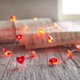 La stringa stellata del cuore rosso illumina il colore bianco caldo piombo su un collegare di rame flessibile