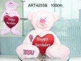 Oso rosado que lleva el regalo rojo de la Corazón-Tarjeta del día de San Valentín