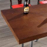 Tabella di legno del nuovo ristorante con la mobilia del giardino esterna
