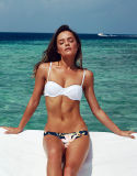 Schönheits-weiße Bikini-Badebekleidung, die Klage-Badebekleidung auf den Strand setzt