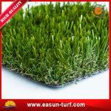 L'erba artificiale di giardinaggio della decorazione copre di tegoli esterno